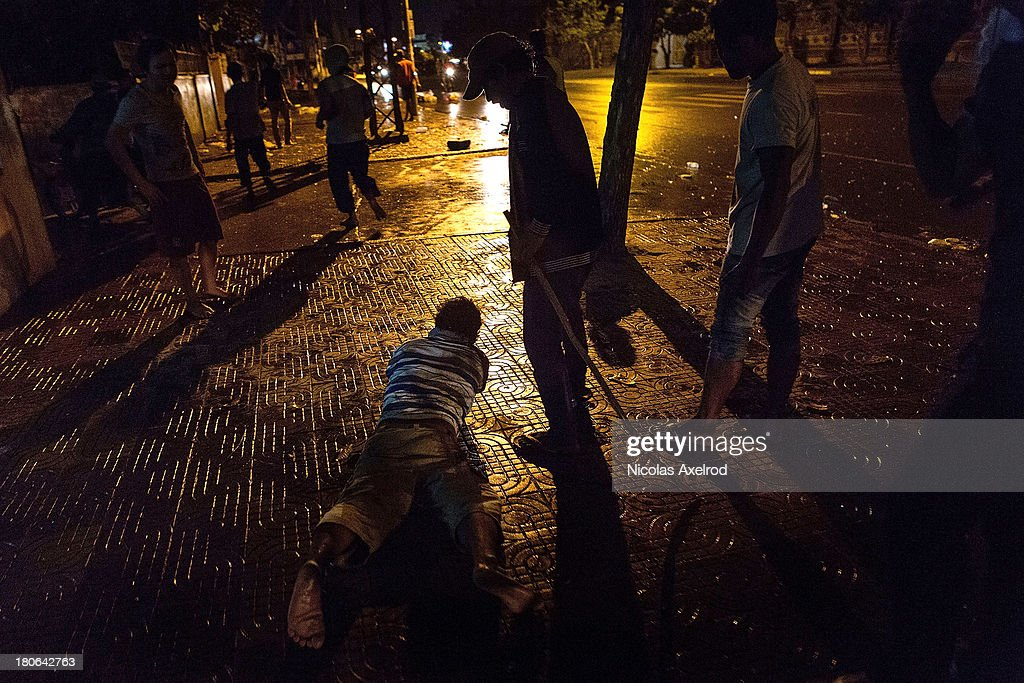 A man lays on the ground after being beaten by anti-riot police, clashes erupted near Monivong bridge South of Phnom Penh on September 15, 2013 in Phnom Penh, Cambodia. The CNRP plan a three day demonstration to contest the Cambodian national election results.