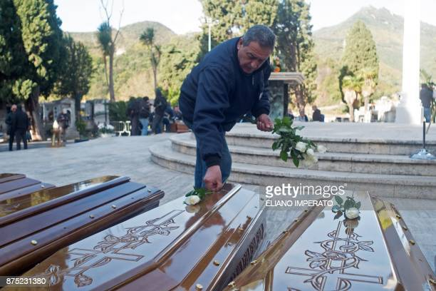 A man lays white roses on the coffins of 26 teenage migrant girls found dead in the Mediterranean in early November before a funeral service on...
