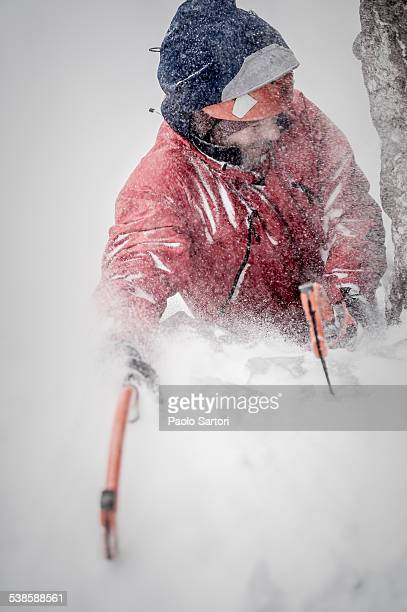 Man lead climbing an ice fall in the middle of a snow storm in Simplon Pass, Valais, Switzerland.