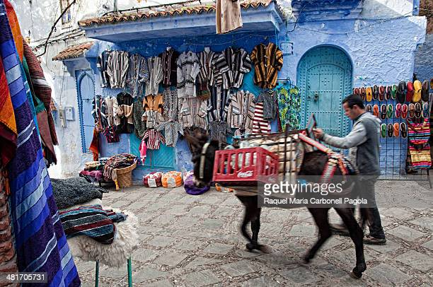 Man leading a donkey and passing by textile shops in the blue medina