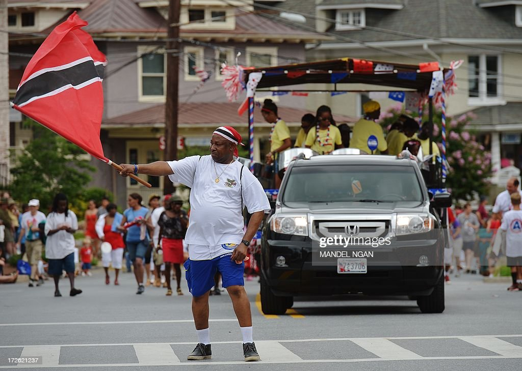 A man leading a steel band waves a flag during the Independence Day parade in Takoma Park Maryland on July 4 2013 Independence Day celebrates the...