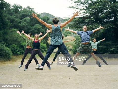 Man leading group of people in boot camp exercises, rear view : Stock Photo