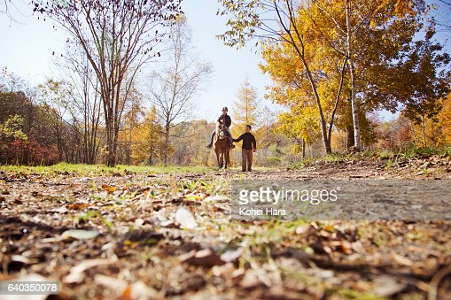 Man leading woman who is riding on horse in the mountain