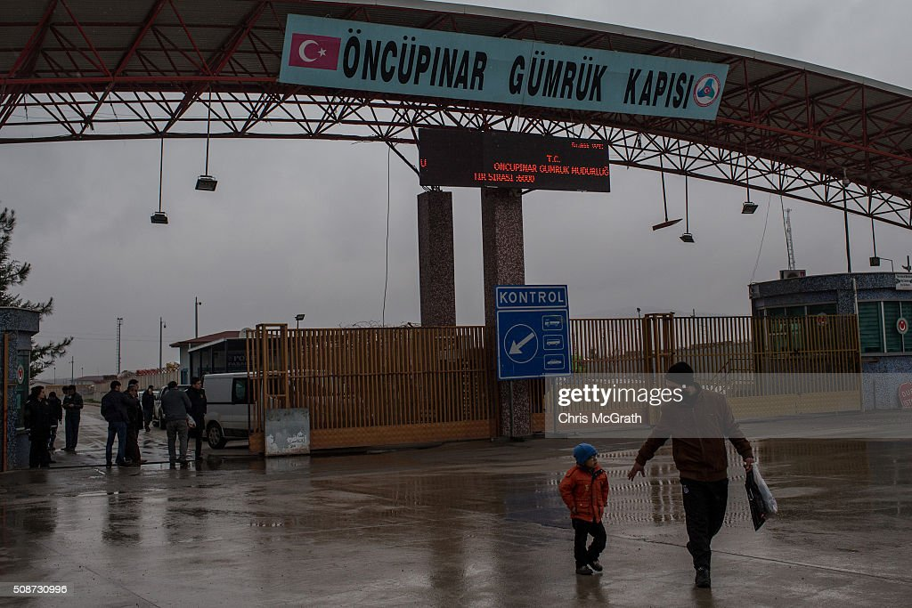 A man leads his son away from the closed Turkish border gate after trying to cross back into Syria on February 6, 2016 in Kilis, Turkey. According to Turkish officials some 35,000 Syrian refugees have massed on the Syrian/Turkish border after fleeing Russian airstrikes and a regime offensive surrounding the city of Aleppo in northern Syria.