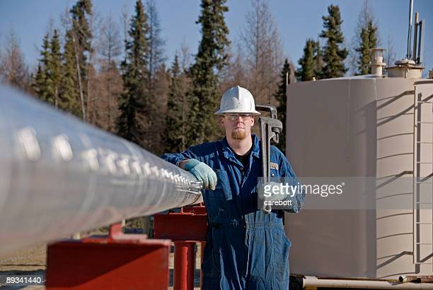 A man leaning against a metal pipe holding a wrench