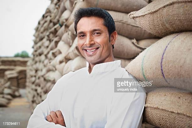 Man leaning against a stack of wheat sacks, Anaj Mandi, Sohna, Gurgaon, Haryana, India