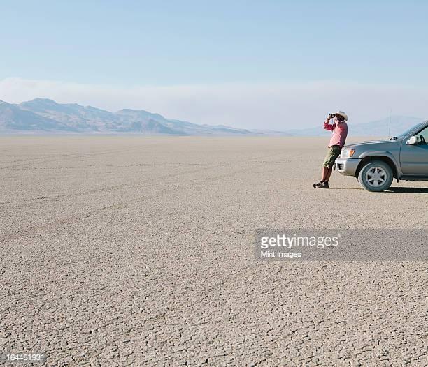 Ein Mann schiefen gegen einen Lkw, Blick durch ein Fernglas einzupacken.