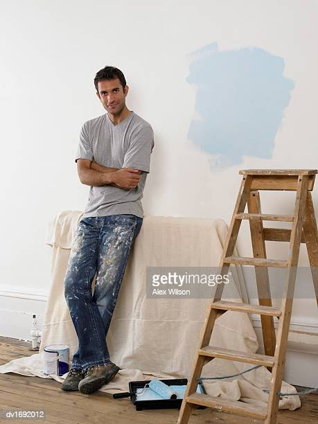 Man Leaning Against a White Wall in a Room Prepared for Decoration, Next to a Step Ladder and Paint Roller