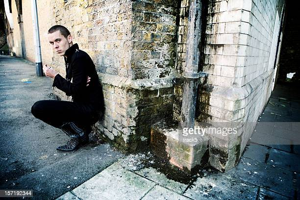 A man leaning against an exterior brick wall