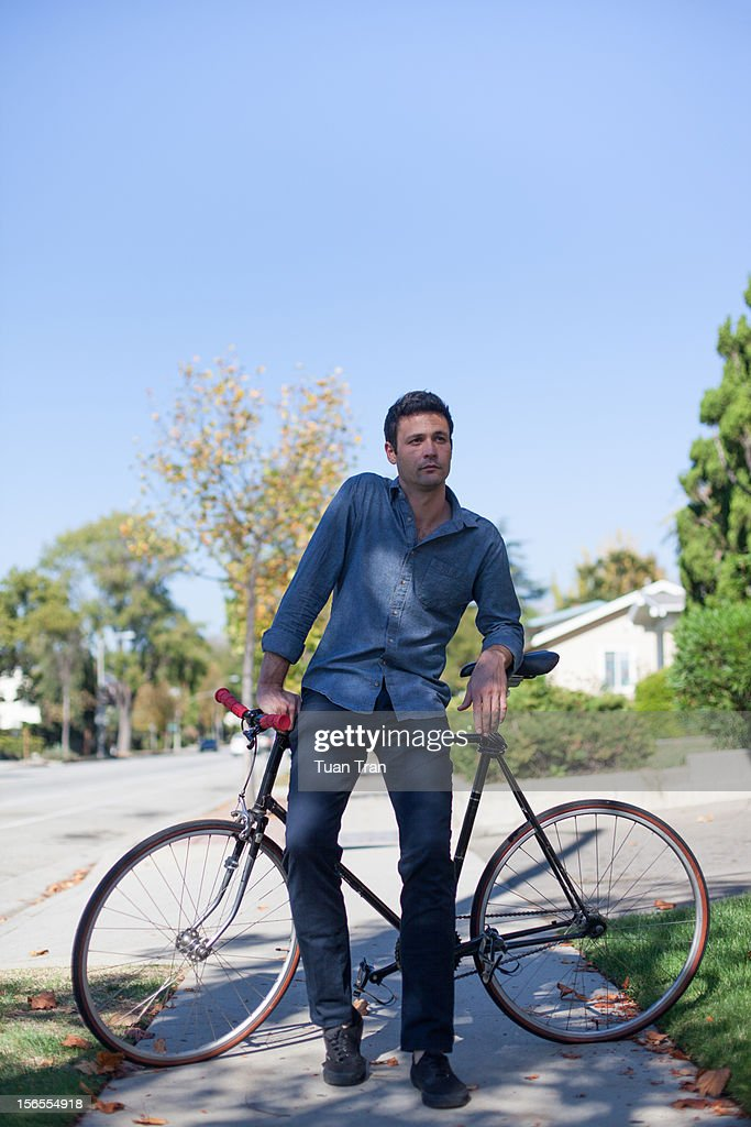 man leaning against bicycle : Stock Photo