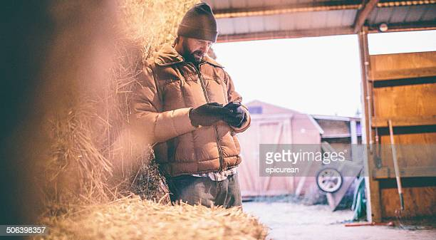 Man leaning against hay in barn looks down at phone