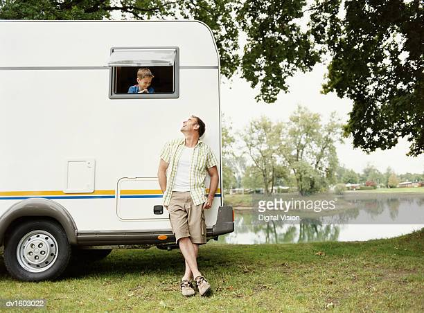 Man Leaning Against His Motor Home Parked Next to a Lake, Looking up at His Young Son Leaning out of the Window