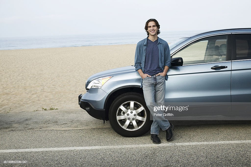 Man leaning against parked car next to beach, portrait : Stock Photo