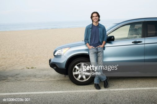 Man leaning against parked car next to beach, portrait : Stock-Foto