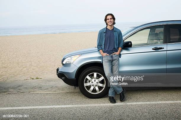 Man leaning against parked car next to beach, portrait