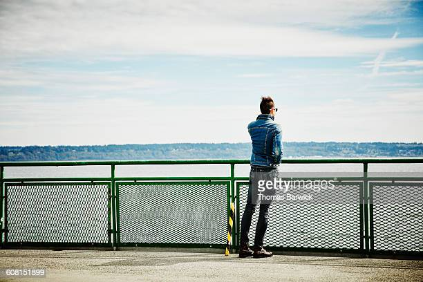 Man leaning against railing on ferry boat