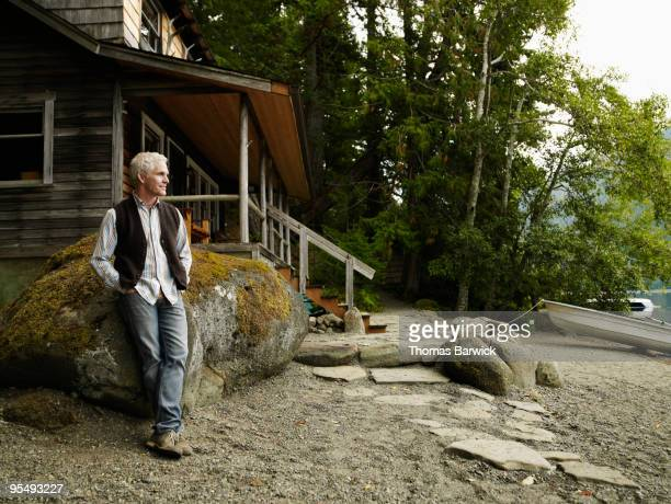 Man leaning against rock in front of cabin on lake