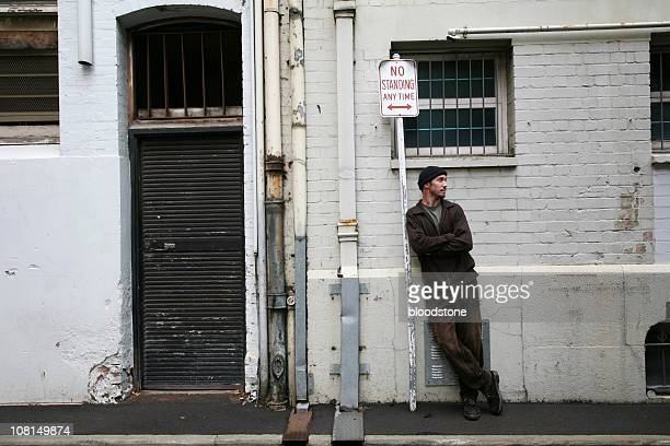 Man Leaning Against Sign and Waiting on Grungy Street