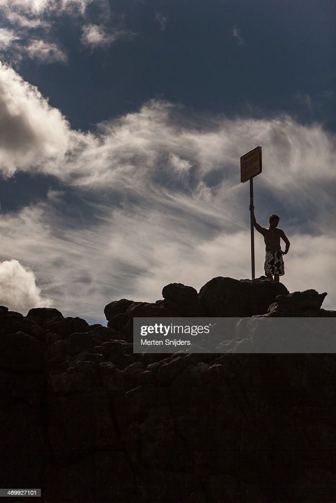 Man leaning against sign on rock : Stock Photo