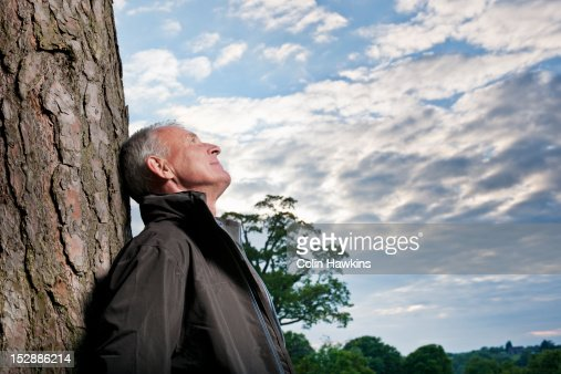 Man leaning against tree outdoors : Stock Photo