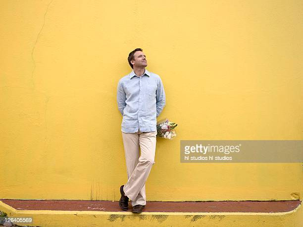 Man leaning against wall and holding bouquet of flowers