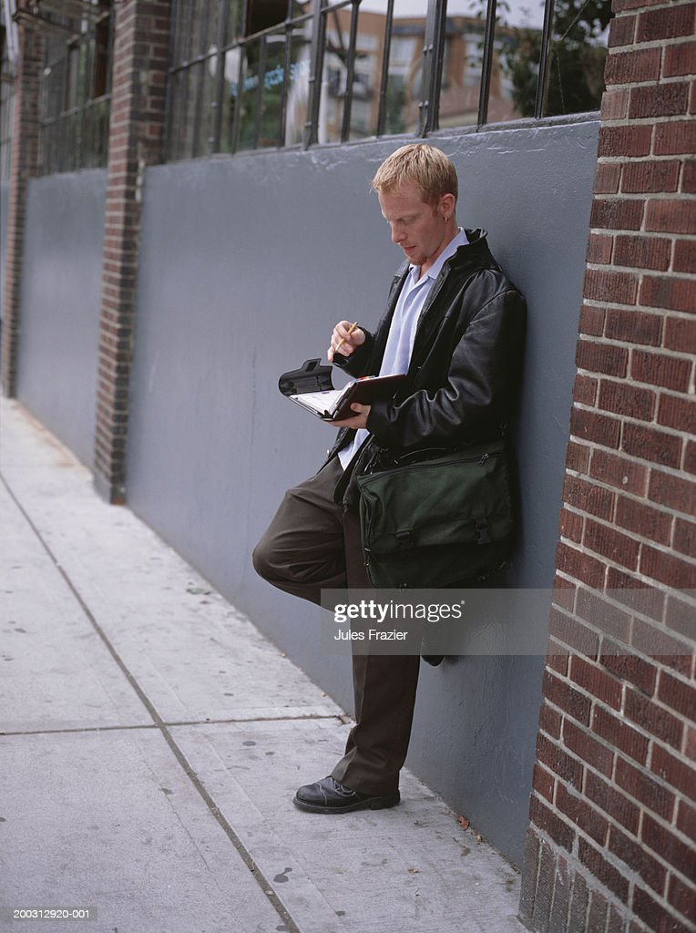 Man leaning against wall outdoors, holding file binder : Stock Photo
