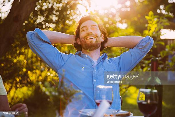 Man leaning back and smiling at dinner in evening light