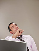 Man leaning back from laptop, holding hand up to chin