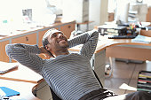 Man leaning back on chair in office, smiling