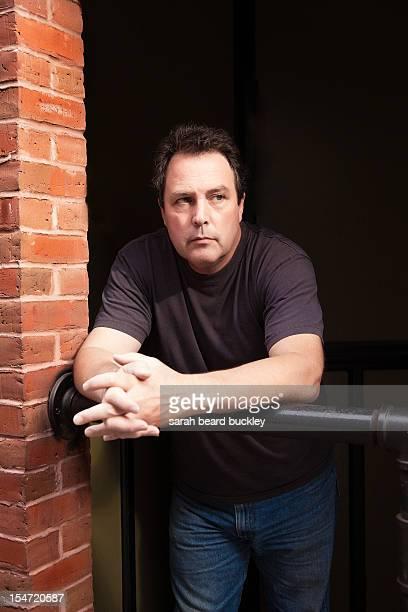 Man leaning near a brick wall