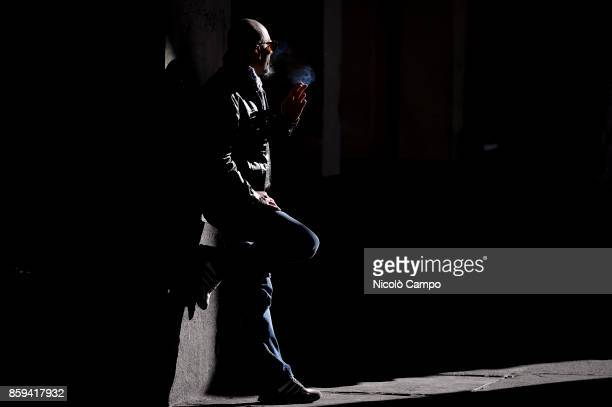 A man leaning on a column smokes a cigarette