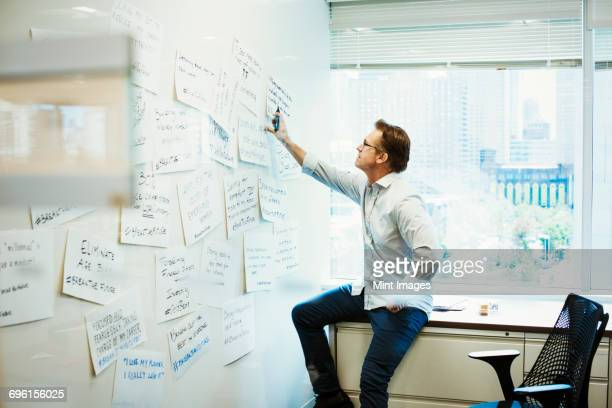 A man leaning on a desk in an office looking at pieces of paper pinned on a whiteboard.