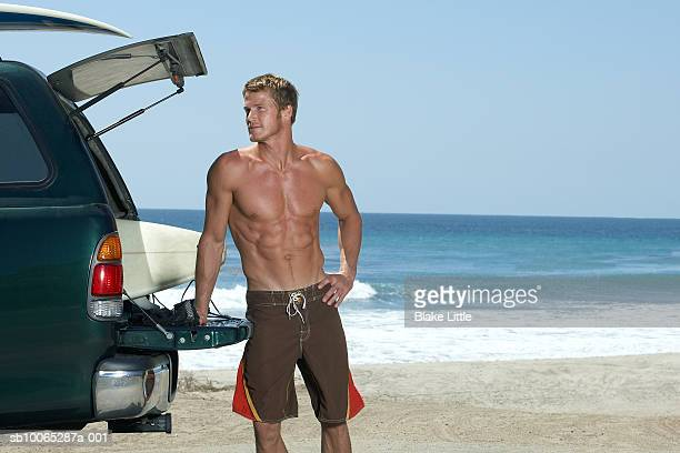 Man leaning on car at beach, looking away