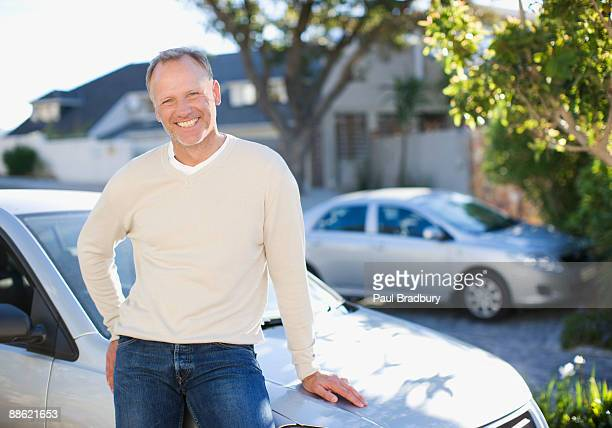 Man leaning on car hood