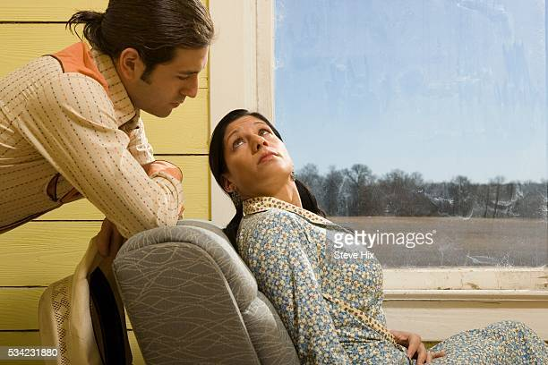 Man Leaning on Chair Back Looking at Woman