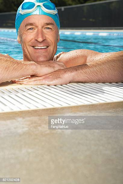 Man leaning on edge of swimming pool