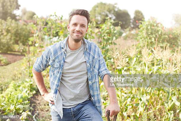 Man leaning on fork in allotment