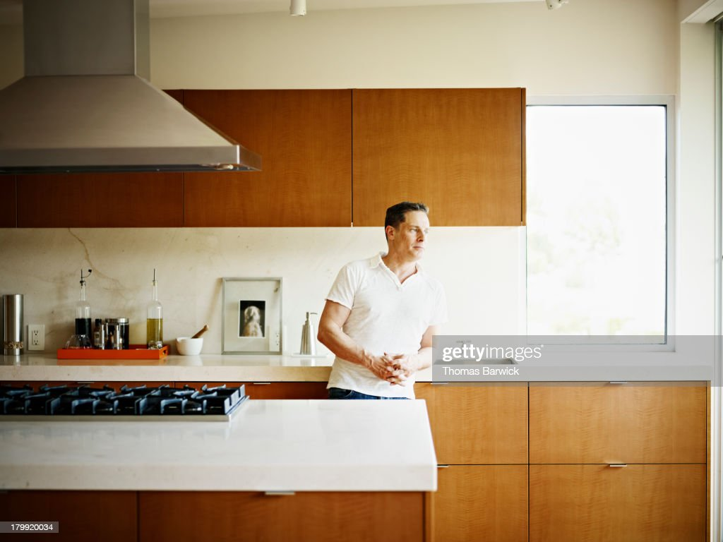 Man leaning on kitchen counter in home : Foto de stock