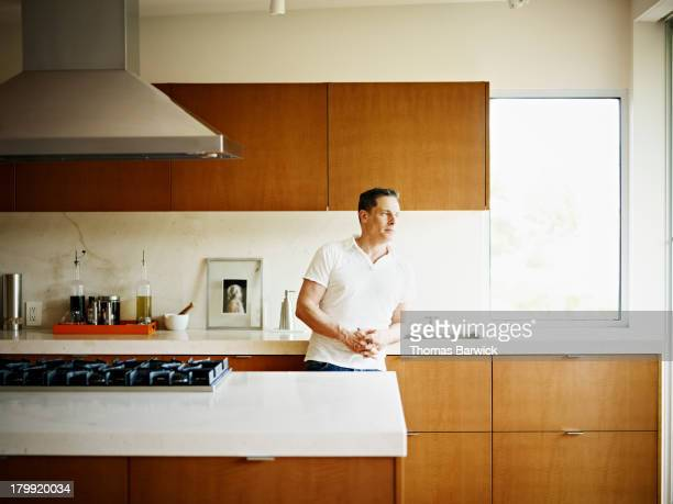 Man leaning on kitchen counter in home