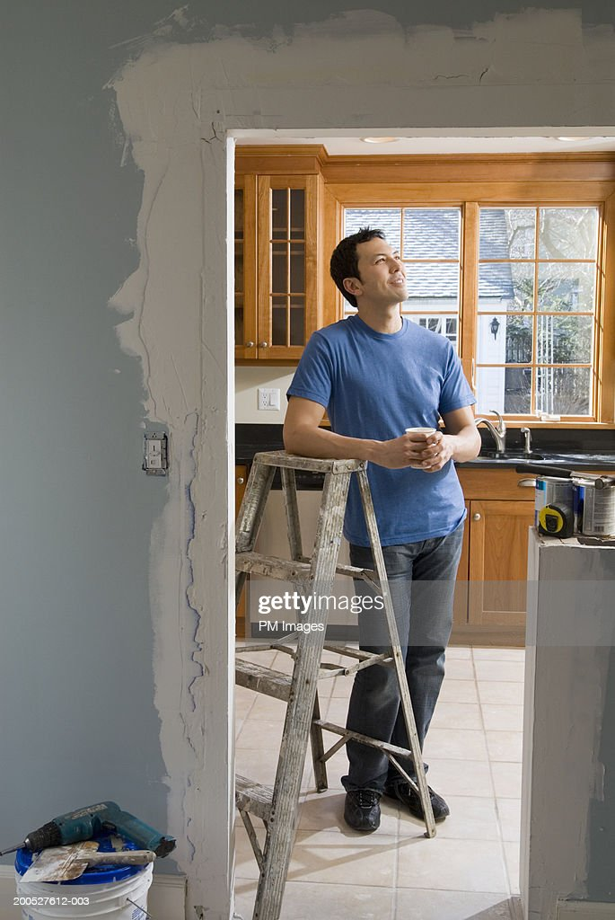 Man leaning on ladder in kitchen, looking up : Stock Photo
