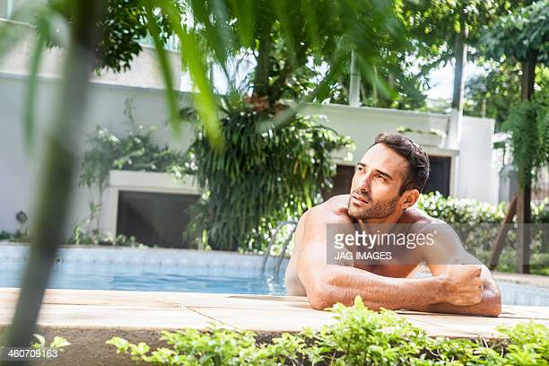 Man leaning on poolside, looking away