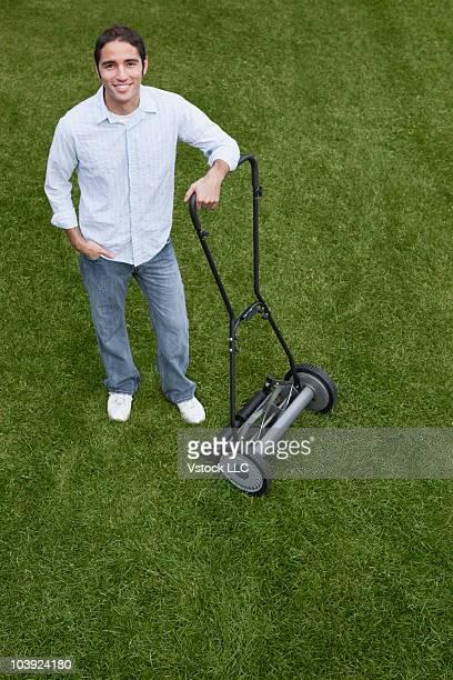 Man leaning on push mower