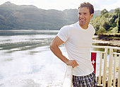 Man leaning on railing by water, smiling