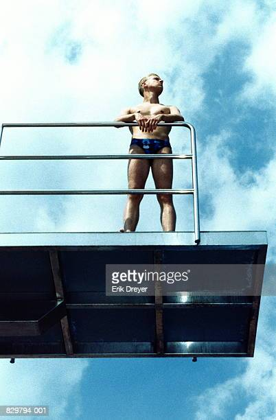 Man leaning on railing on diving board, low-angle view