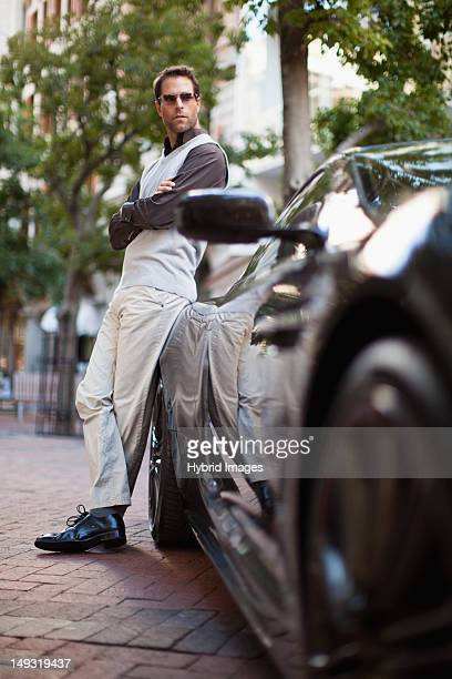 Man leaning on sports car