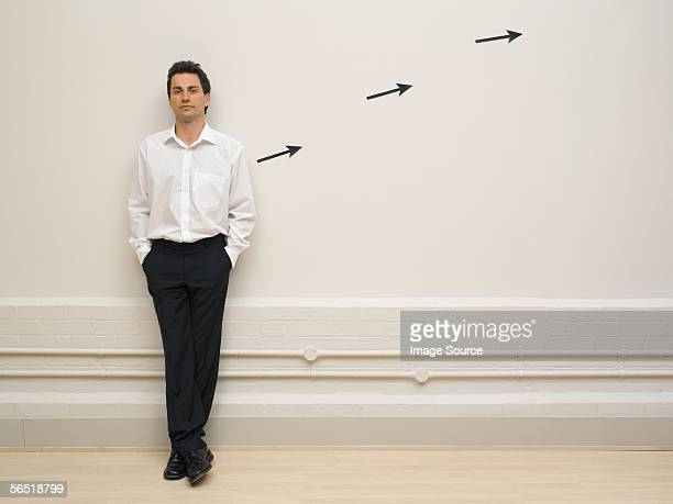 Man leaning on wall by arrow signs