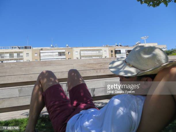 Man Leaning On Woman Leg Against Wall