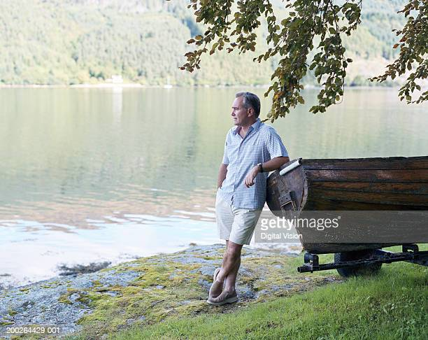 Man leaning on wooden boat by river