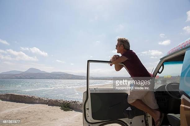 Man leans across van door, looks out across sea