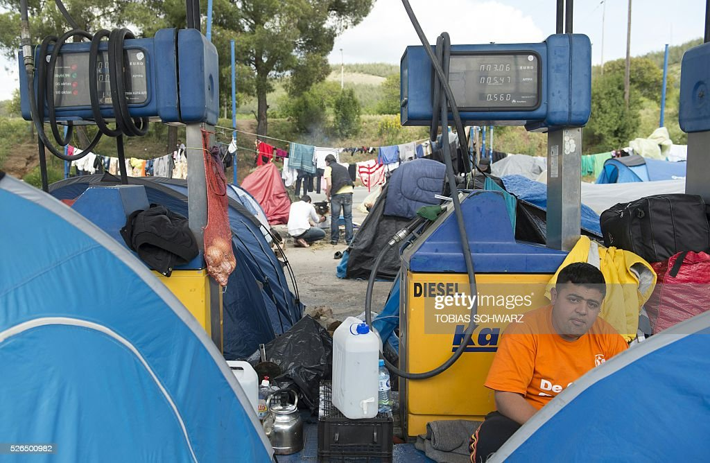 A man leans against a fuel pump at a makeshift camp in a gas station for migrants and refugees near the village of Idomeni not far from the Greek-Macedonian border on April 30, 2016. Some 54,000 people, many of them fleeing the war in Syria, have been stranded on Greek territory since the closure of the migrant route through the Balkans in February. / AFP / TOBIAS